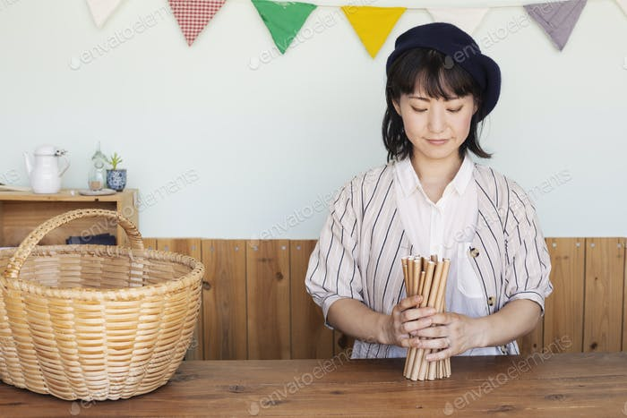 Japanese woman standing next to a basket behind counter in a farm shop.