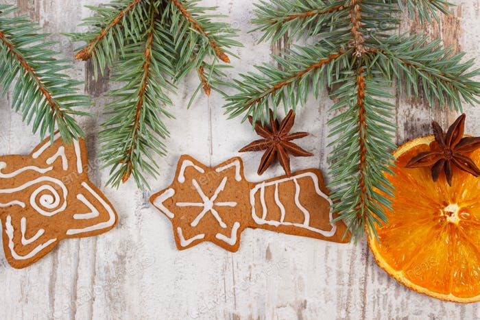 Fresh baked gingerbread, spruce branches and spices on old board, christmas decoration