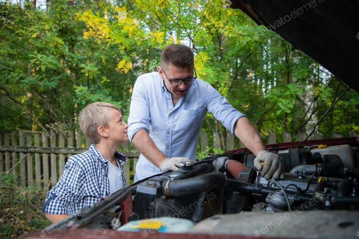 Young father teaching his son to change motor oil in family car.