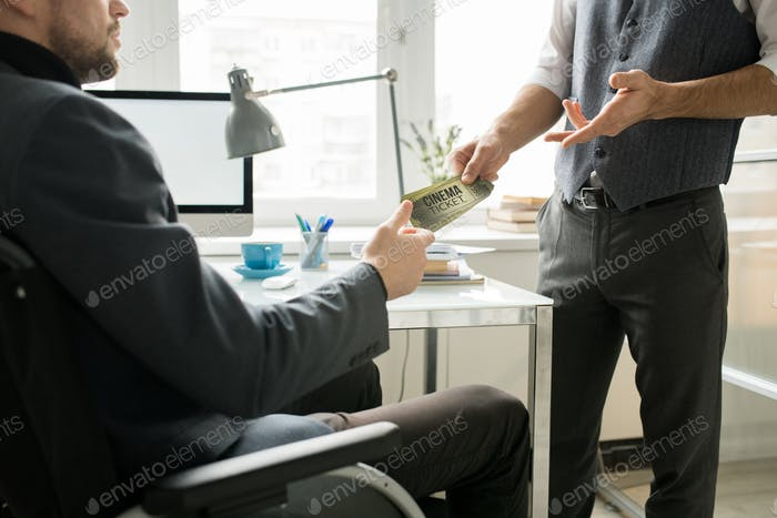 Giving the movie tickets to colleague