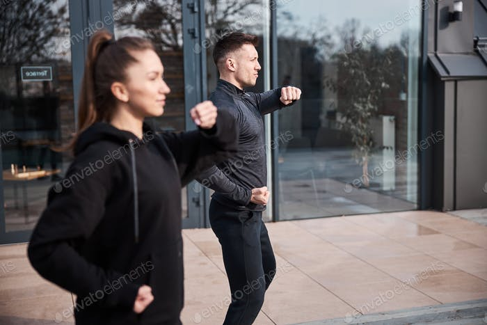 Outside terrace with people training wushu pose