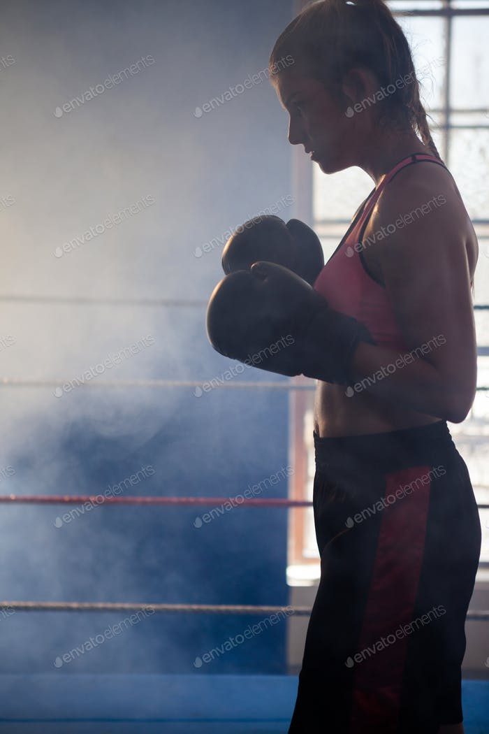 Determined woman standing in boxing ring