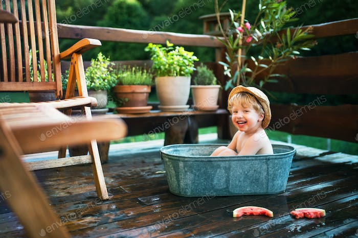 Small boy with a hat and watermelon in bath outdoors in garden in summer.