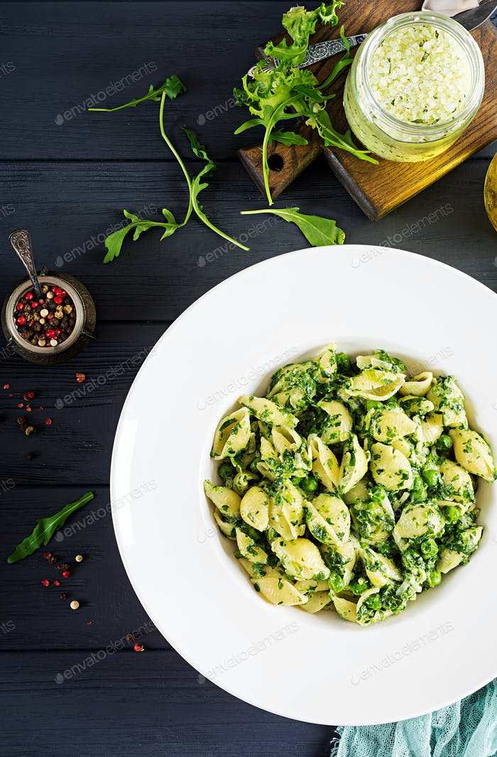 Conchiglie pasta with spinach and green pea pesto. Italian Cuisine. Vegan food. Top view