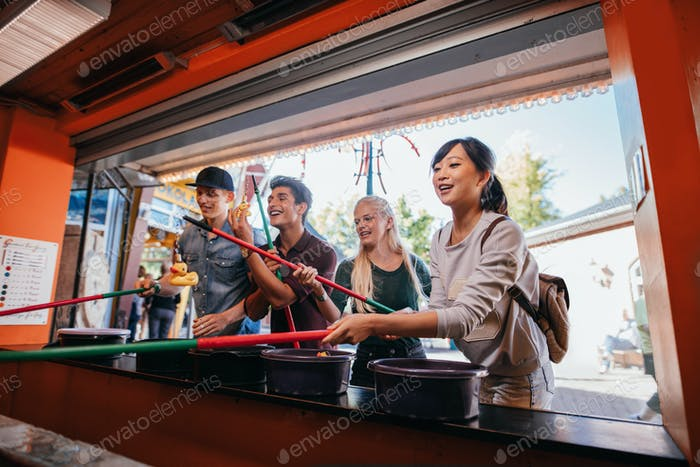 Multiracial friends playing arcade game at amusement park