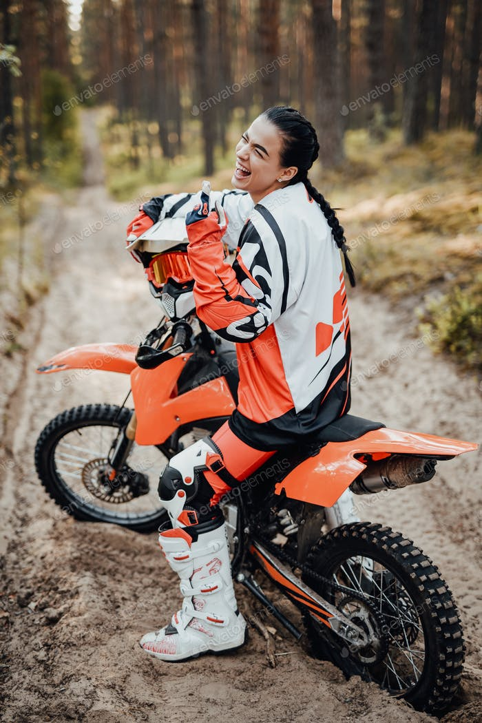 Happy female racer wearing motorcycle outfit sitting on her bike off-road in the woods