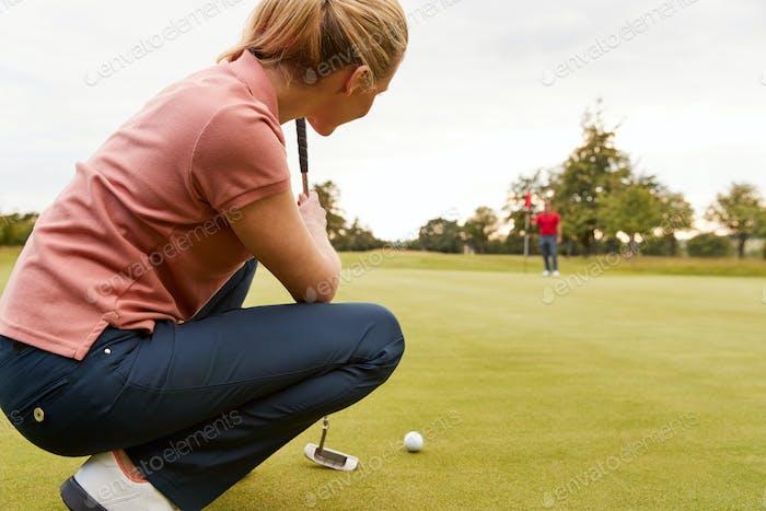 Weibliche Golfer Lining Up Shot On Putting Green As Man Tends Flag