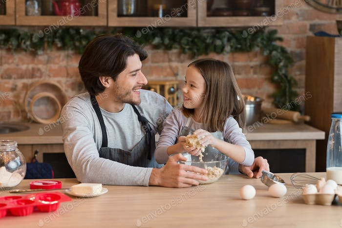 Loving dad cooking with his adorable daughter, teaching how to knead dough
