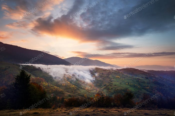 Bright colorful sunrise in mountains with smoke and dramatic bright sky