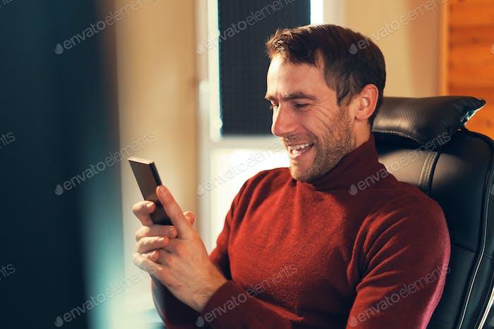 Ein Mann, der gerne gute Nachrichten erhält, während er auf das Smartphone schaut