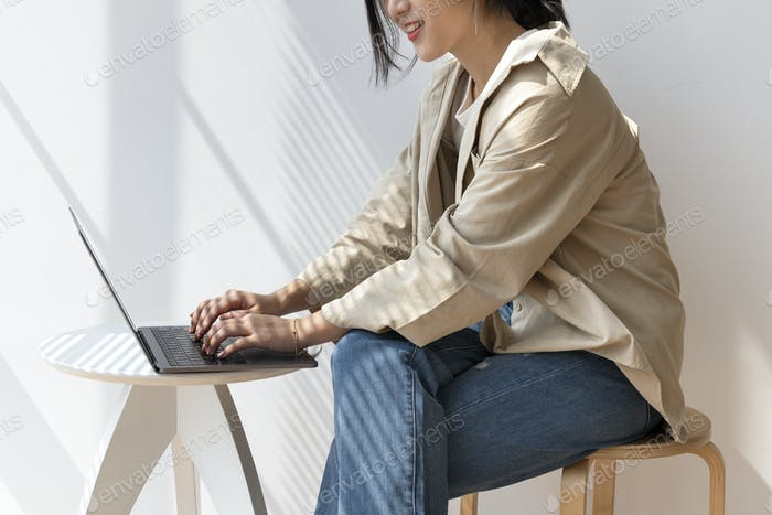 Asian woman working on her laptop in a cafe