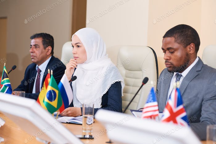 Pensive young female delegate in hijab listening to one of colleagues