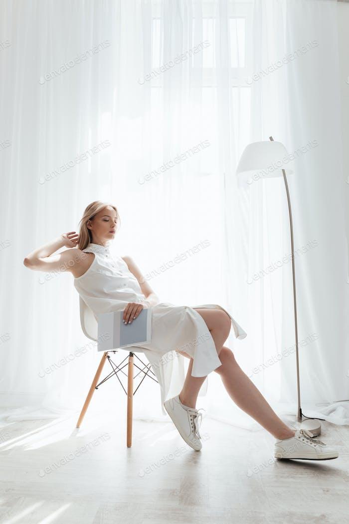 Schöne blonde Dame sitzen drinnen gekleidet in weißen Kleid