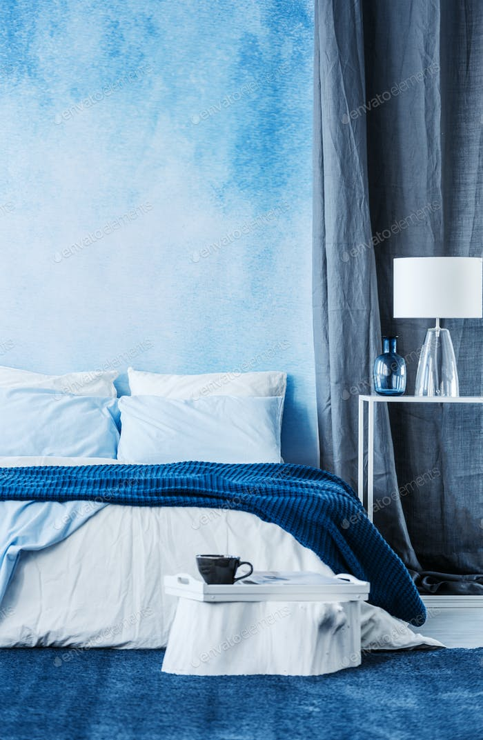 Blue watercolor paint on the wall in modern bedroom interior wit