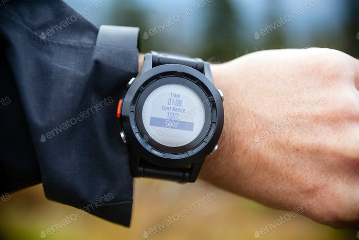Hiker on mountain trail checking compass, wearable technology
