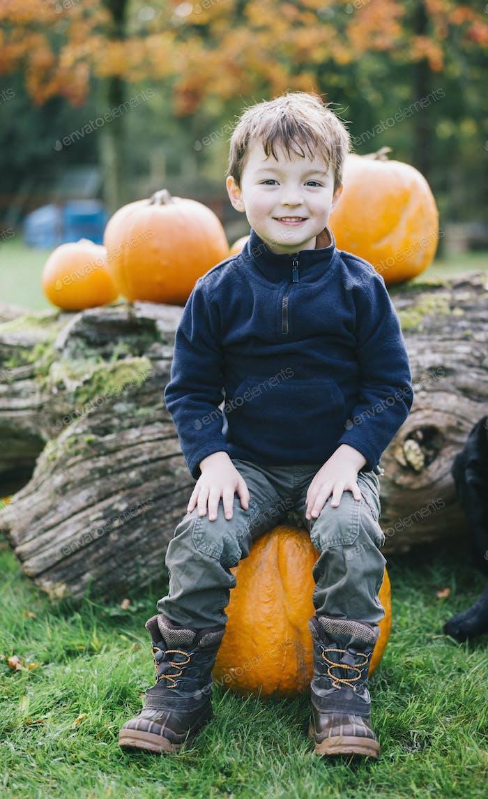Ein Junge sitzt auf einem großen orangefarbenen Kürbis bei der Kürbisernte.