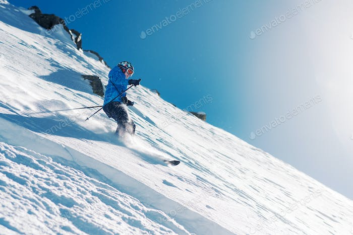 girl with special ski equipment is riding very fast in the mountain hill