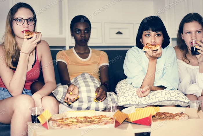 A diverse group of women sitting on the couch and eating pizza together