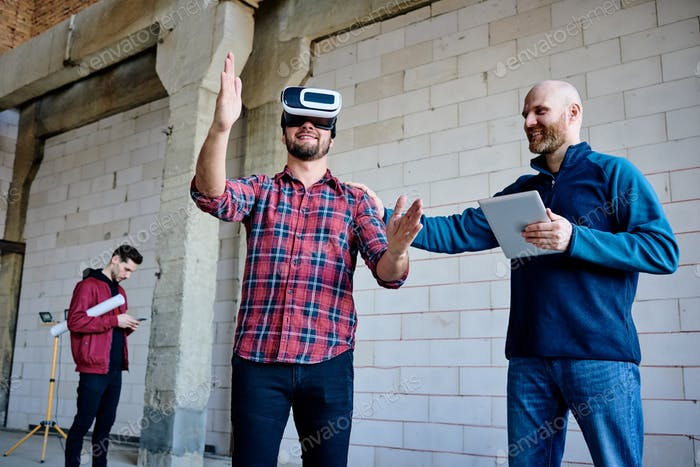 Young engineer in vr headset making presentation of new furnishing materials