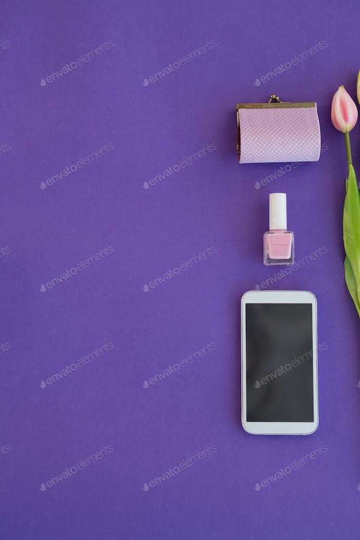 Tulpen, Geldbörse, Nagellack und Handy angeordnet auf lila Hintergrund