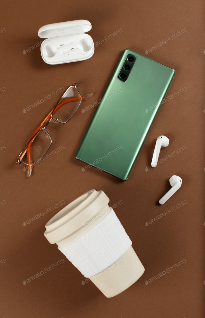 Smartphone, reusable coffee to go cup, wireless earphones and glasses