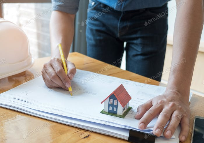 Architect holding a yellow pencil drawing house plan with model house.