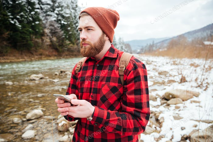Thoughtful male hiker holding smartphone