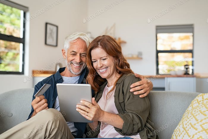 Mature couple doing online shopping with digital tablet