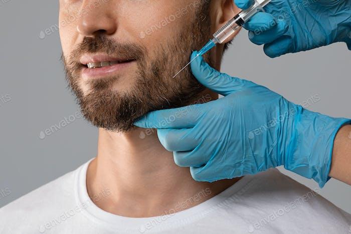 Unrecognizable bearded man getting beauty injection in salon