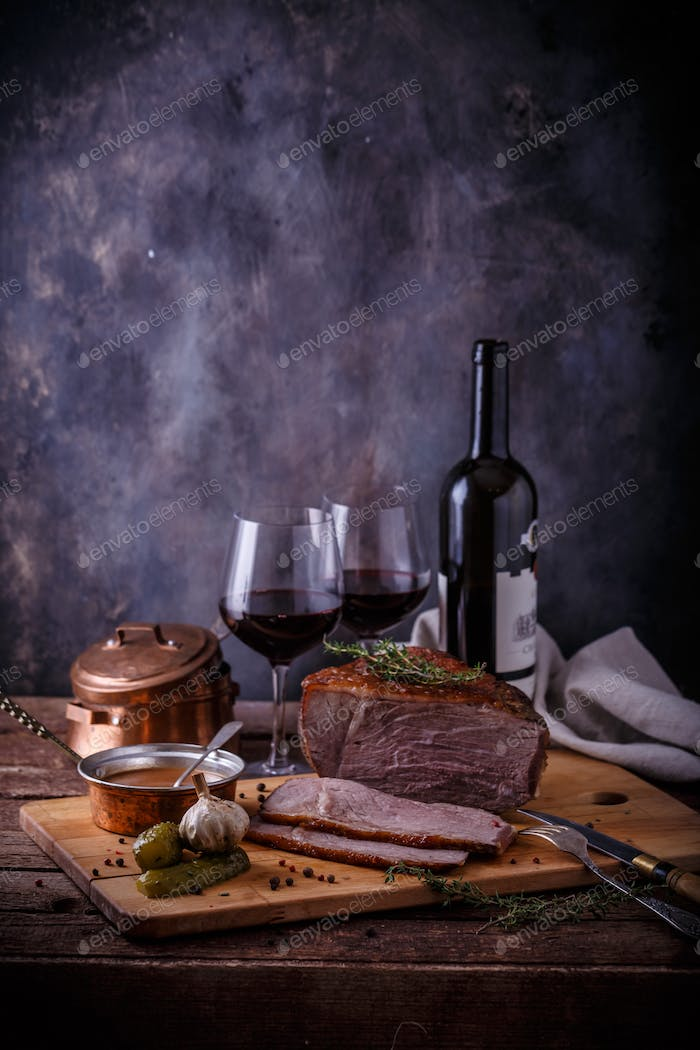 Baked beef on wooden cutting board with sauce, pickles and wine, copy space