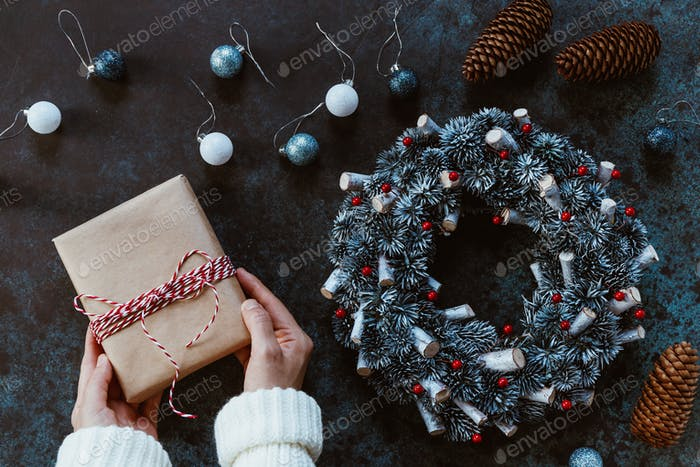 Girl's hands in a winter white sweater hold a New Year's gift box