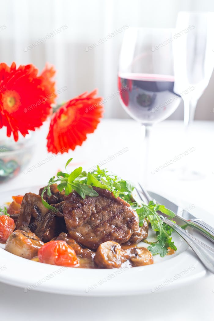 The concept of Italian cuisine. Juicy steak of beef aging stewed meat, with rucola salad and cherry