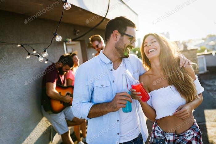 Freunde, die Spaß haben und draußen trinken auf einem Dach zusammen