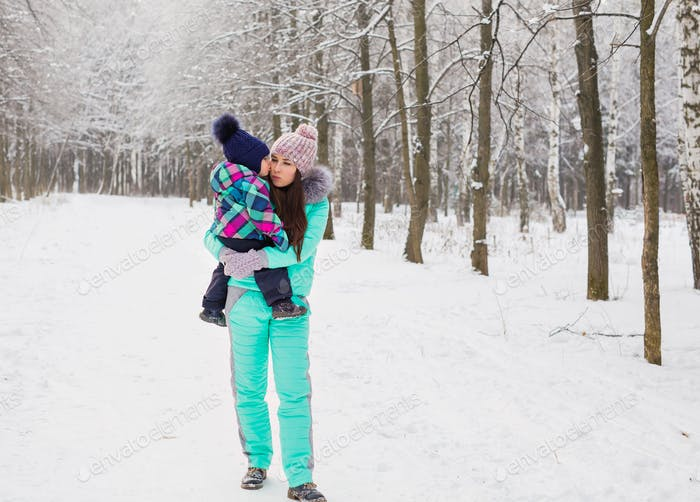 happy family mother and baby girl daughter playing and laughing in winter outdoors in the snow.