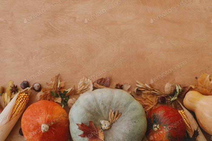 Happy Thanksgiving flat lay. Pumpkins, autumn leaves, corn, walnuts