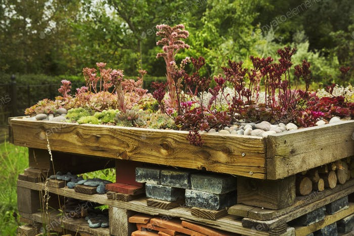 Close up of large bug house with several layers of different materials in a garden.