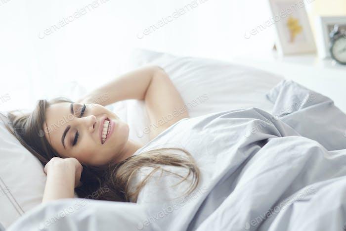 mujer sonriente acostado en el dormitorio