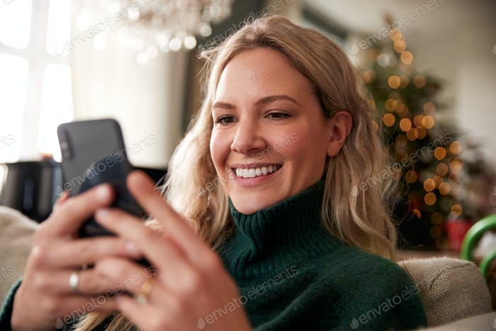 Close Up Of Woman Relaxing On Sofa At Home At Christmas Using Mobile Phone