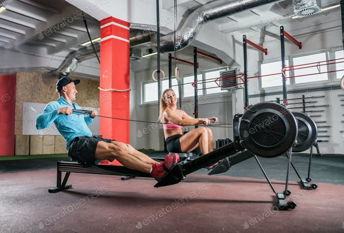 Entrenamiento de pareja de fitness en la máquina de fila en el gimnasio de cross