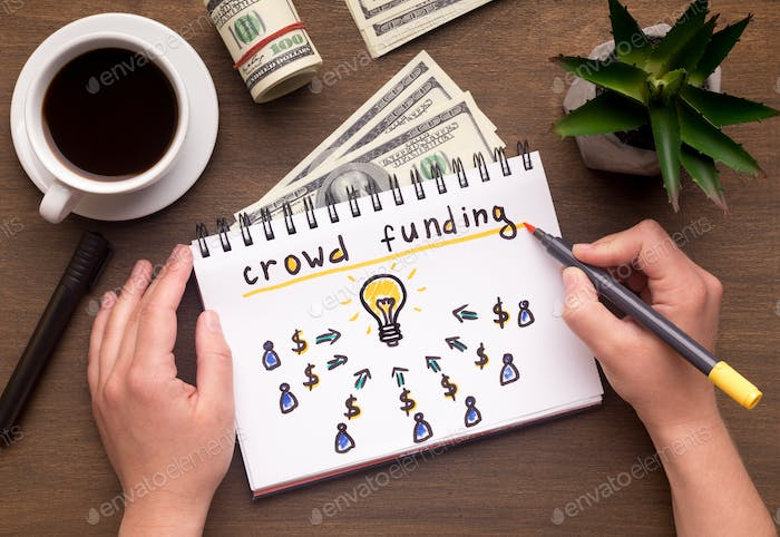 Woman hand writing in notebook crowdfunding sign on table