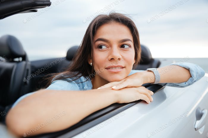 Portrait of smiling woman sitting in her convertible car