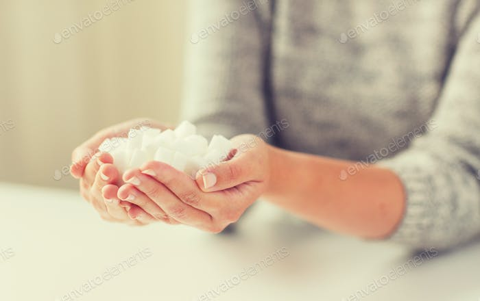 close up of white lump sugar in woman hands