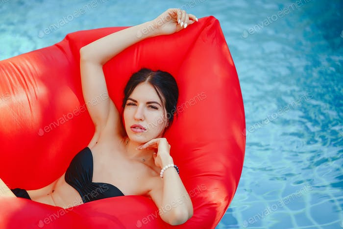 brunette girl relaxing in the pool