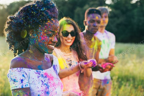 multicultural friends with colorful paint on clothing and bodies at holi festival