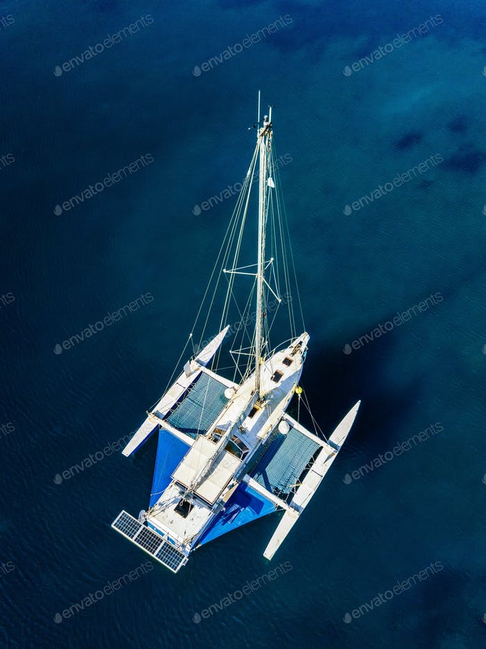 Aerial view of catamaran anchoring on coral reef.