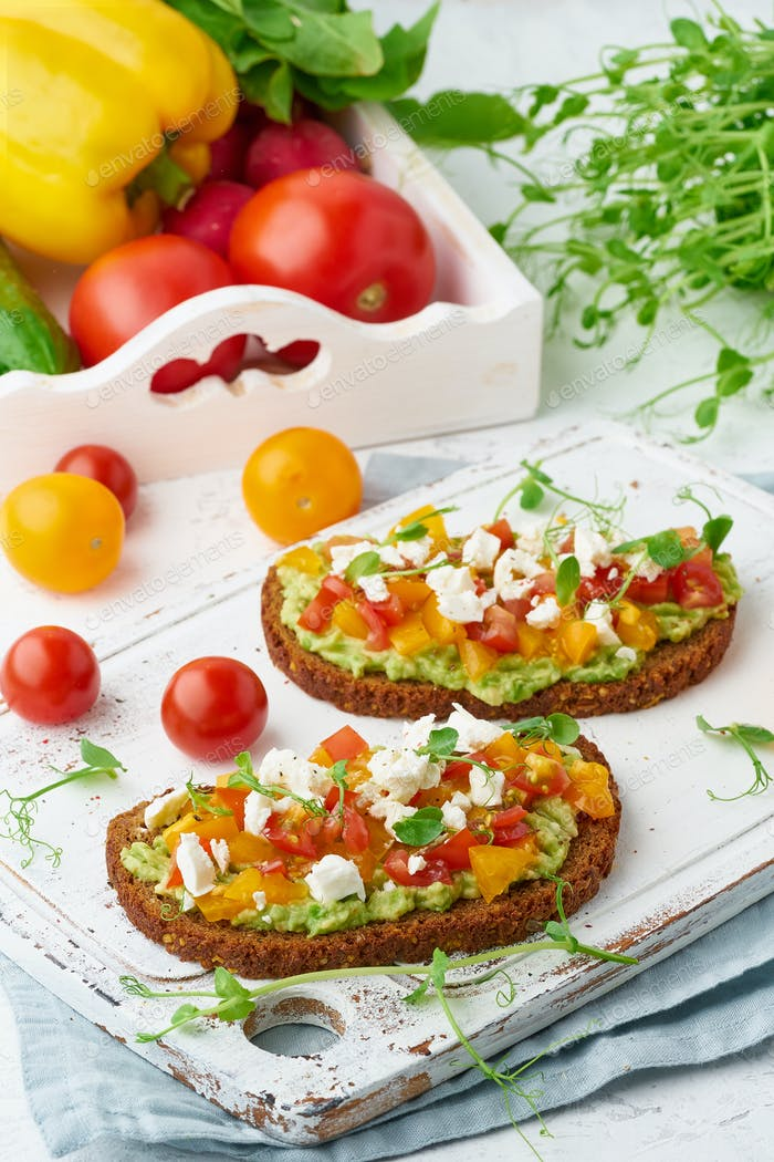 avocado toast with feta and tomatoes, smorrebrod with ricotta, closeup and vertical