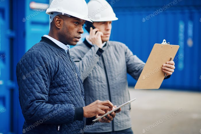Engineers working together in a large commercial shipyard