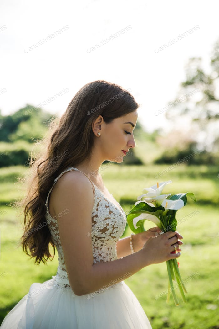 Young beautiful bride holding bouquet. Soft sunset light