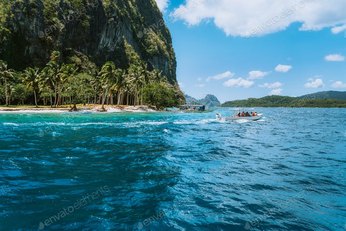 Boat with tourists on ipil beach of exotic island on hopping tour, Bacuit archipelago, El Nido