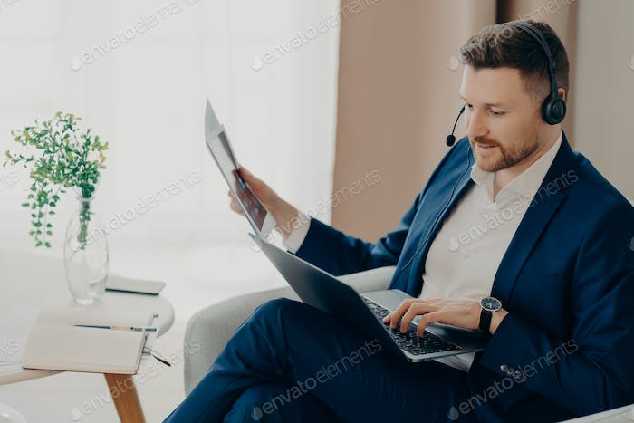 Busy young businessman working with documents at home remotely